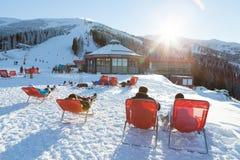 CHOPOK SLOVAKIEN - JANUARI 12, 2017: Skidåkare och snowboarders som tar en vila i stolar nära apres, skidar stången nära Chopok m Royaltyfria Bilder