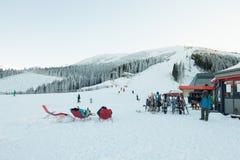 CHOPOK SLOVAKIEN - JANUARI 12, 2017: Snowboarders och skidåkare som tar en vila i stolar nära apres, skidar stången som är längst Royaltyfria Foton