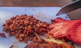 Chopped烤了在白色切板的牛排用在红色橡胶的手在露指手套和刀子-特写镜头&选择聚焦 库存照片