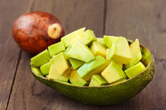 Chopped avocado fruit on brown wooden old table Royalty Free Stock Images