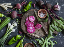 Chopped beets, peppers, onions, green beans, spices on a dark background. Fresh garden vegetables. Stock Photography