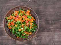 Chopped bell pepper, parsley and olive oil on a wooden table. royalty free stock image