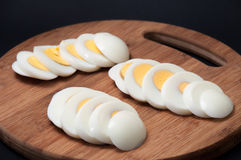 Chopped and boiled eggs arranged on a kitchen wooden board Royalty Free Stock Photography