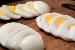 Chopped and boiled eggs arranged on a kitchen wooden board Royalty Free Stock Images