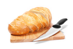 Chopped bread with knife on wooden utensil Royalty Free Stock Image