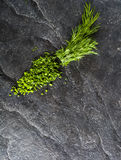 Chopped bunch of fresh dill on a black stone background. Stock Images