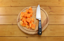 Chopped butternut squash with a knife on a chopping board Royalty Free Stock Image