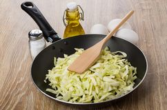 Chopped cabbage in frying pan, vegetable oil, salt, eggs Stock Image