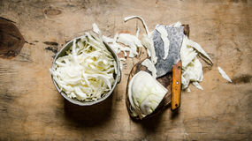 Chopped cabbage in a pot and an old hatchet. Stock Images