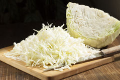 Chopped cabbage strips and a head of cabbage. Royalty Free Stock Images