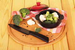 Chopped cauliflower in bowl and knife on wooden table Royalty Free Stock Photo