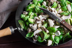 Chopped champignons and brussels sprouts in large skillet with knife, prepared for cooking Royalty Free Stock Image