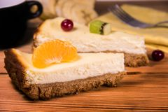 Chopped cheesecake on a wooden table with fruit, a towel and a cup of coffee royalty free stock photo