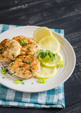 Chopped chicken cutlets with lemon and cilantro. On a light plate Royalty Free Stock Images