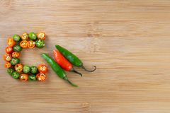 Chopped chili pepper red and green on wooden surface stock photos
