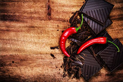 Chopped Chocolate Bar With Red Chilli Pepper On Wooden Background Closeup. Chunks Of Broken Dark Chocolate Bar On Wood Table Royalty Free Stock Photography