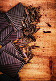Chopped Chocolate Bar on wooden background closeup. Broken dark Stock Images