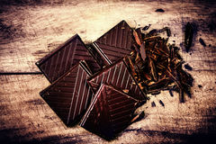 Chopped Chocolate Bar on wooden background closeup. Broken dark. Chocolate bar on wood table macro Royalty Free Stock Images