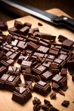 Chopped chocolate bar on wooden chopping board Royalty Free Stock Photography