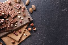 Chopped chocolate bars with nuts. On gray background Royalty Free Stock Photos