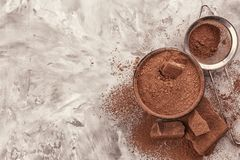 Chopped chocolate chunks and bowl. With  cocoa powder on table Stock Photography