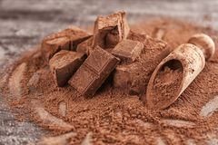 Chopped chocolate chunks, cocoa powder. And wooden scoop on table Royalty Free Stock Images