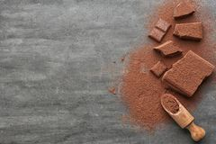 Chopped chocolate chunks, cocoa powder. And wooden scoop on table Stock Image