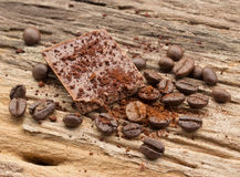 Chopped chocolate and coffee bean with cocoa on wood. Background Royalty Free Stock Images