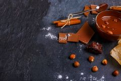 Chopped chocolate with hazelnuts, around sweets on a stone background royalty free stock photo