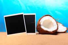 Chopped coconut and photoframe on the sand Royalty Free Stock Images