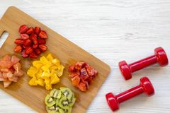Chopped colorful raw fruits and dumbbells on white wooden background, top view. Copy space Stock Photography