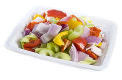 Chopped Colorful Raw Vegetables. Chopped colorful vegetables on a white plate, isolated on white Royalty Free Stock Images