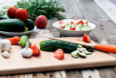 Chopped cucumber and tomato salad on a cutting board Stock Photography