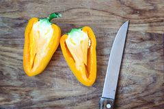 Chopped cut colorful vibrant bright yellow fresh ripe sweet pepper on old cutting wooden board table background Stock Photo