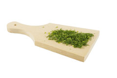 Chopped dill on a wooden board. Isolated cutting board with green chopped herbs Royalty Free Stock Photography