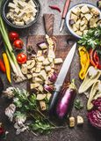 Chopped eggplant on wooden cutting board with knife and various vegetarian cooking ingredients for healthy eating , top view. Balk Stock Photo