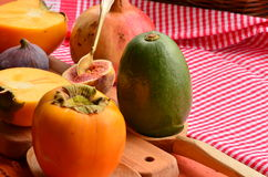 Chopped fig and persimmon on chopping board Royalty Free Stock Image