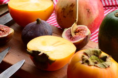 Chopped fig and persimmon on chopping board Royalty Free Stock Images