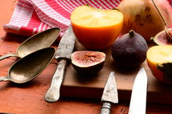 Chopped fig and persimmon on chopping board Stock Photos