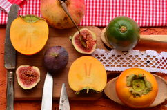 Chopped fig and persimmon on chopping board. Vintage theme Stock Image