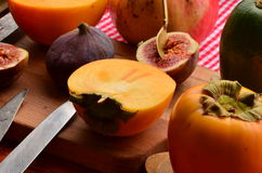 Chopped fig and persimmon on chopping board. Vintage theme Royalty Free Stock Image