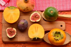 Chopped fig and persimmon on chopping board. Vintage theme Royalty Free Stock Photo
