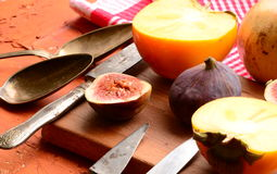 Chopped fig and persimmon on chopping board. Vintage theme Stock Photo