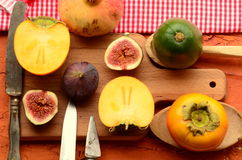 Chopped fig and persimmon on chopping board. Vintage theme Royalty Free Stock Photography