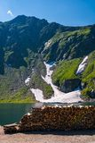 Chopped firewood on the shore of a glacier. Beautiful summer scenery in mountains. rocky hill with some grass and spots of snow Stock Photo