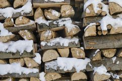 Chopped firewood on a stack in snow. Front view stock photo