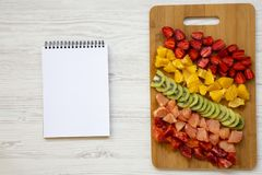 Chopped fresh colorful fruits arranged on cutting board with notepad on white wooden background,. Top view royalty free stock photo