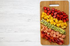 Chopped fresh colorful fruits arranged on cutting board on white wooden background, top view. Copy space and text area. Flat lay. stock photos