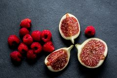 Chopped fresh figs and raspberries. Good quality large size photo of chopped fresh figs and bright red raspberries plated on black shale surface. You may see Royalty Free Stock Photo