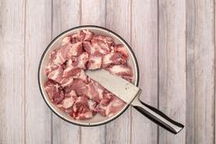 Chopped fresh meat in a frying pan. With a knife on wooden planks Stock Photo